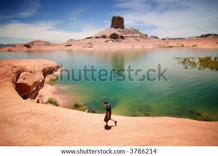hiker walks past an emerald lagoon in lake powell - stock photo