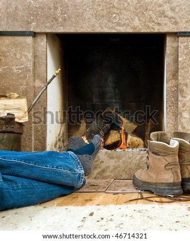 Hiker warming uyp and relaxing by a small fireplace - stock photo