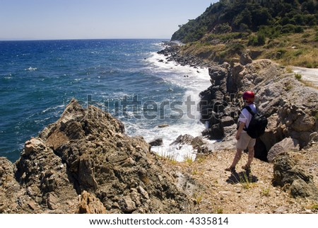 Hiker watching the sea from the top of a rock. Samos Island, Greece