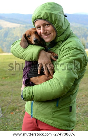 Hiker with a dachshund keep warm hugs - stock photo