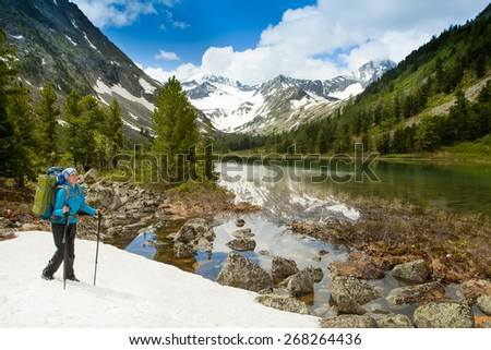 Hiker with backpack and trekking sticks to overcome difficulties in the mountains in Altai mountains, Russian Federation - stock photo