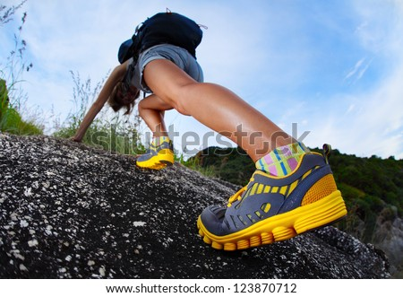 Hiker with backpack climbing rocky terrain. Focus on the boot - stock photo