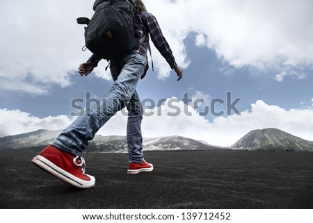 Hiker with backpack crossing valley covered with ash towards volcano - stock photo