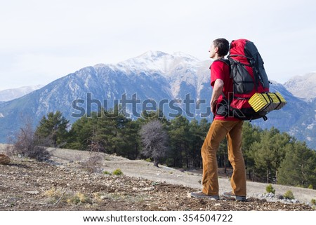 Hiker  with backpack  enjoying valley view from top of a mountain