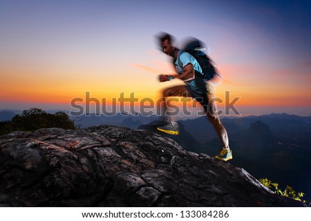 Hiker with backpack reached top of a mountain at sunrise. Motion blurred elements. Feet, hand, shoulder and part of face are in focus. - stock photo