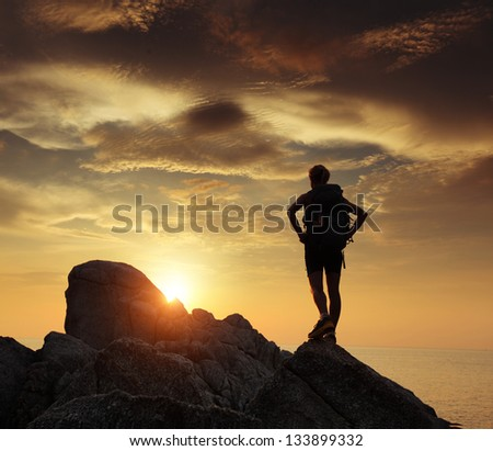 Hiker with backpack relaxing on a rock and enjoying sunset - stock photo