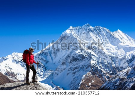 Hiker with backpack relaxing on top of a mountain and enjoying valley view
