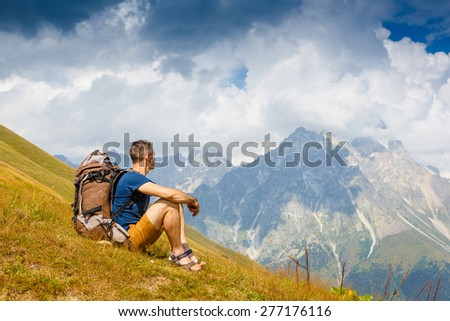 hiker with backpack sitting and enjoying the view  - stock photo