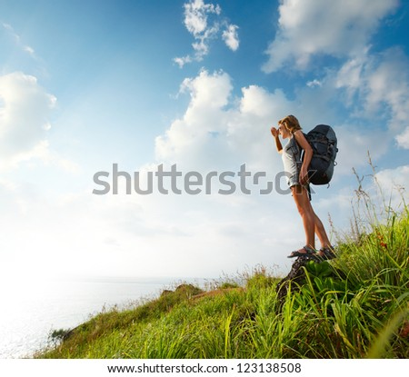 Hiker with backpack standing on a rock and looking to somewhere