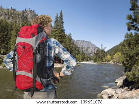 Hiker, with backpack, standing on the banks of the Wenatchee River, near Leavenworth in the Cascade Mountain range, Washington State, USA - stock photo