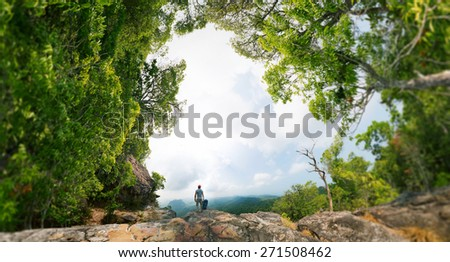 Hiker with backpack standing on the rock surrounded by lush tropical forest. Edges of image are blurred - stock photo