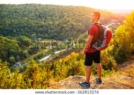 Hiker with backpack standing on top of a mountain - stock photo