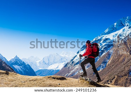 Hiker with backpack standing on top of a mountain and enjoying. Himalayas   - stock photo