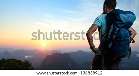 Hiker with backpack standing on top of a mountain and enjoying sunrise. - stock photo