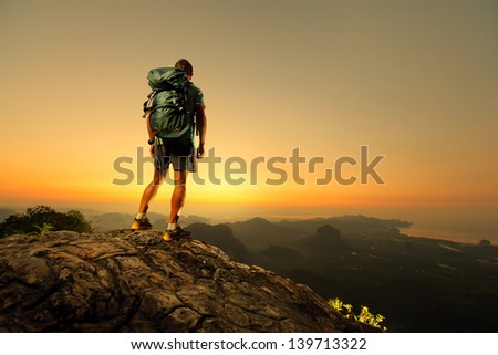 Hiker with backpack standing on top of a mountain and enjoying sunrise - stock photo