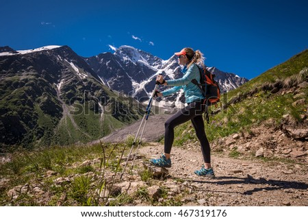 "Hiker with backpack standing on top of a mountain and enjoying valley view.  Beautiful landscape of glacier ""Seven"" on Mount Donguzorun, Kabardino-Balkaria republic, Elbrus region"