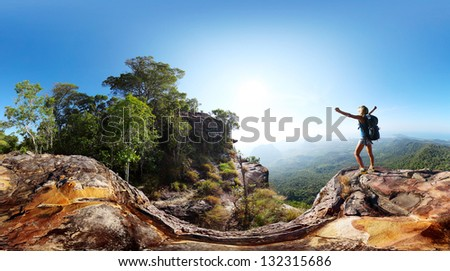 Hiker with backpack standing on top of a mountain with raised hands and enjoying sunrise - stock photo