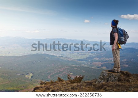 Hiker with backpack standing on top of the mountain and looks into the distance.Freedom concept. Autumn mountain travel.  - stock photo
