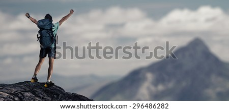Hiker with backpack standing on top of the mountain with raised hands - stock photo
