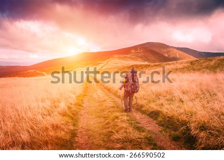 Hiker with backpack walking the treck to the top of mountain - stock photo