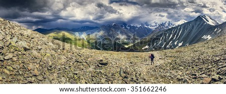 Hiker with backpack walks along a range in the altai mountains  - stock photo