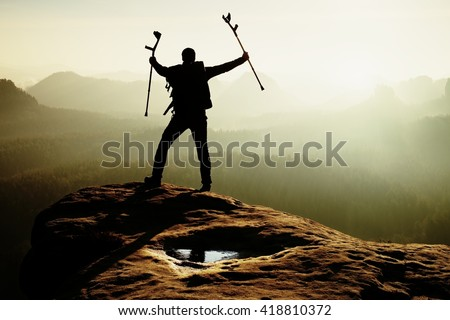 Hiker with broken leg in immobilizer and medicine pole above head achieved rocky summit. Deep misty valley bellow sharp edge. Silhouette of tourist with hand in air. Spring daybreak - stock photo