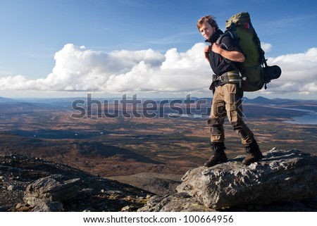 Hiker with huge backpack on the mountain top - stock photo