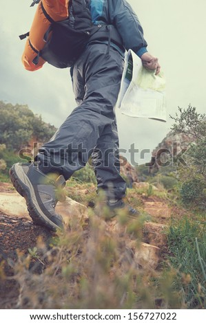 Hiker with map and backpack in outdoors lifestyle - stock photo