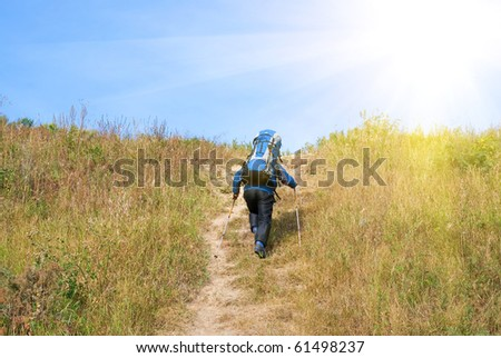 Hiker with rucksack up-hill at summer sunny day - stock photo