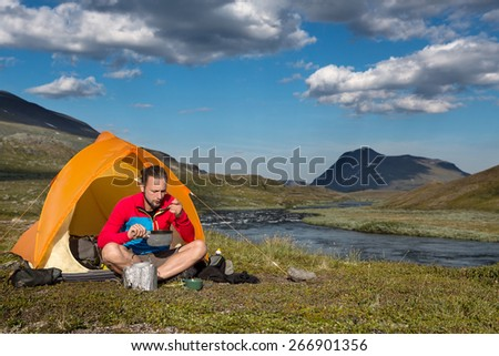 Hiker with tent on a camp in the wilderness of sweden - stock photo