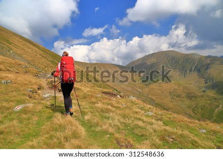 Hiker woman carries a backpack on a mountain trail  - stock photo
