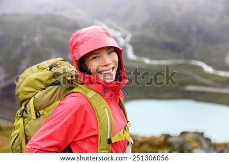 Hiker woman hiking with backpack in rain on trek living healthy life. Smiling fresh and candid young asian girl walking on hike in mountain nature landscape while raining in Swiss alps, Switzerland. - stock photo