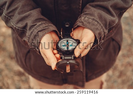 Hiker woman holding a compass on nature - stock photo