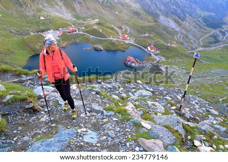 Hiker woman on rocky mountain trail high above glacier lake surrounded by chalets  - stock photo