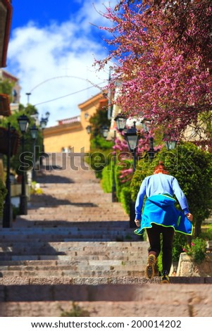 Hiker woman running uphill on the scending street in the mountain town of Arachova, Greece - stock photo