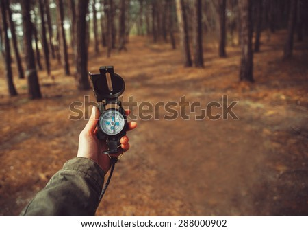Hiker woman searching direction with a compass in the forest. View of hands. Point of view shot. Space for text in right left of image - stock photo