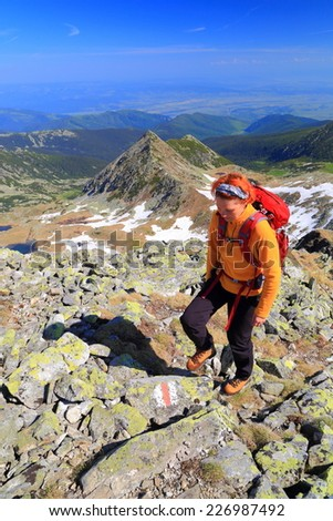 Hiker woman stepping on granite boulders on sunny morning - stock photo
