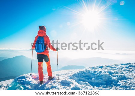 Hiker  woman trekking on the snow in a snowy mountain in winter - stock photo