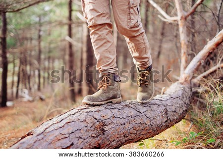 Hiker woman walking on tree trunk in the forest outdoor. View of legs. Hiking and leisure theme