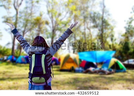 Hiker woman with arms raised and blurred camping tents in forest. - stock photo