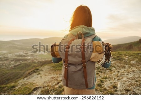 Hiker woman with backpack and sleeping bag walking in the mountains in summer at sunset - stock photo