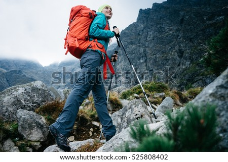 Hiker woman with backpack walking up the trail with beautiful mountain peaks view landscape.  Hiking in a stormy weather, active lifestyle. Achievement and success.