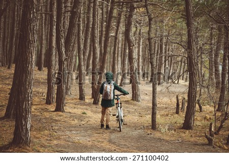 Hiker woman with backpack walking with bicycle in pine forest - stock photo