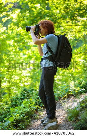 Hiker woman with camera and backpack on a trail in mountains - stock photo