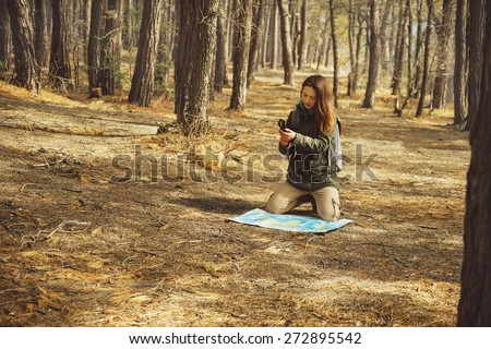 Hiker young woman searching direction with a compass and map in the forest - stock photo