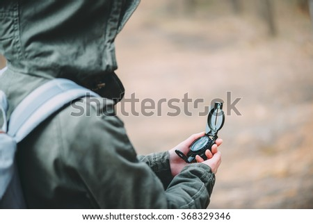 Hiker young woman searching direction with a compass in the forest, close-up - stock photo