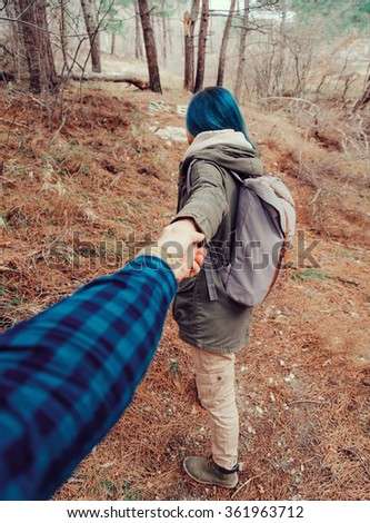 Hiker young woman with backpack holding man's hand and leading him in the forest outdoor. Point of view shot