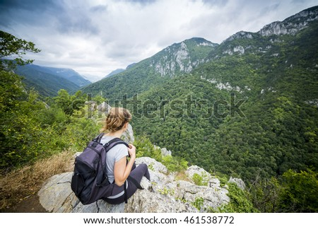 Hiker young woman with backpack sitting on a rock while admiring the view