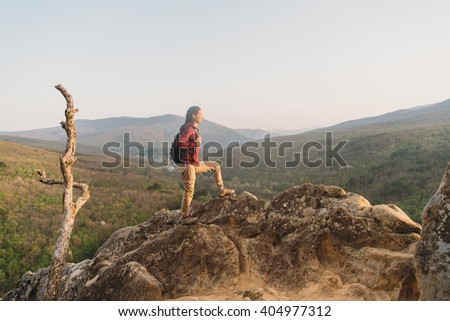 Hiker young woman with backpack standing on peak of rock on background of mountains and looking into the distance in summer outdoor - stock photo