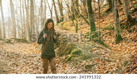 Hiker young woman with backpack walking in beautiful autumn forest. Hiking and leisure theme. Image with sunlight effect - stock photo